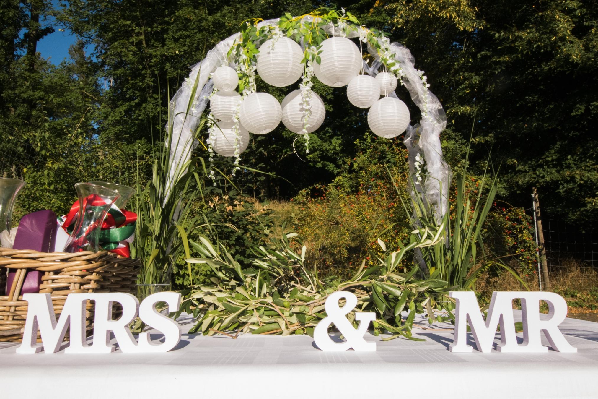 Deko Mr & Mrs Hochzeitsbogen mit runden Lampen im freien